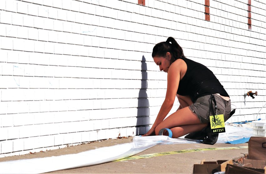 Artist Marissa Napoletano puts down plastic sheeting and masking tape before she begins to paint her building at the corner of 72nd and Hooker St. Aug. 13.