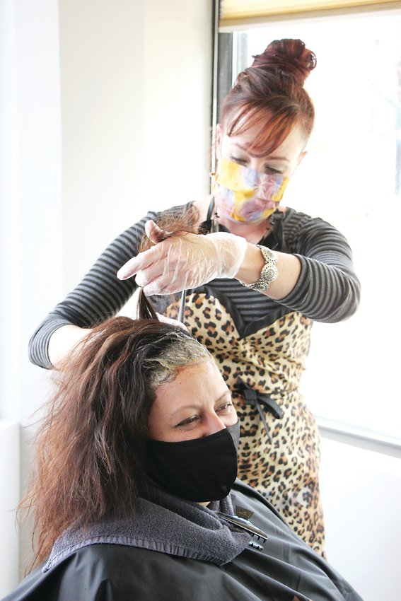 In a May 2020 file photo, hairstylist Jen Ambrose works with longtime client Teresa Caldaro at Indulgence Salon on Main Street in Littleton. Colorado is under a statewide order requiring people to wear masks in public indoor spaces.