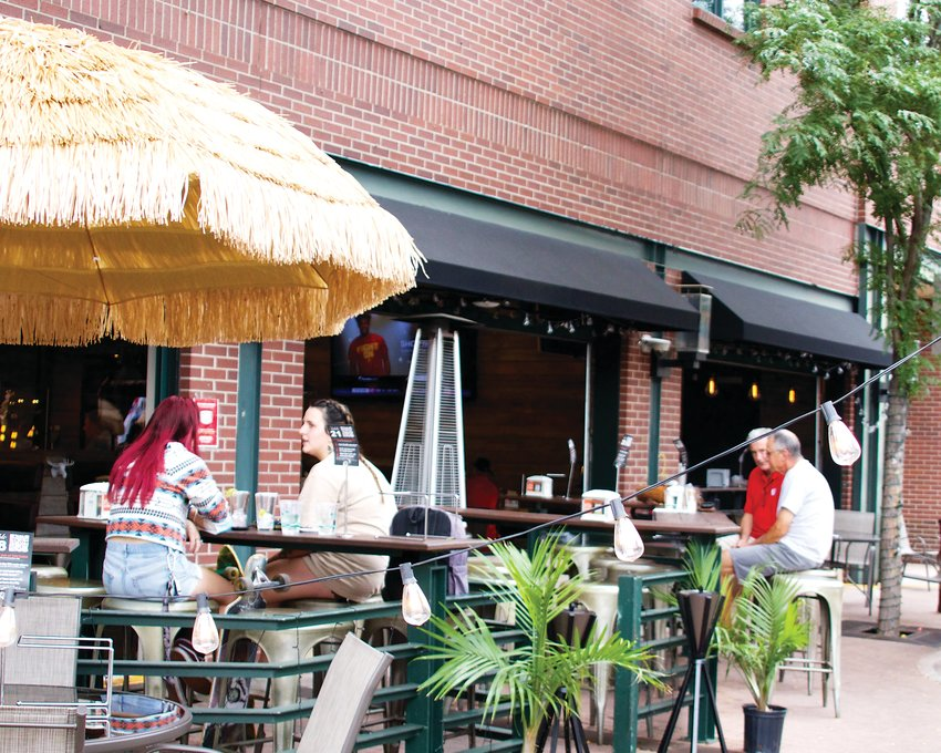 Residents enjoy socially distanced meals on the patio of Homegrown Tap & Dough on Olde Wadsworth Boulevard. The restaurant is one of many in Olde Town that has expanded its patio to accommodate more customers through Olde Town's street closures, which will now last through early November.