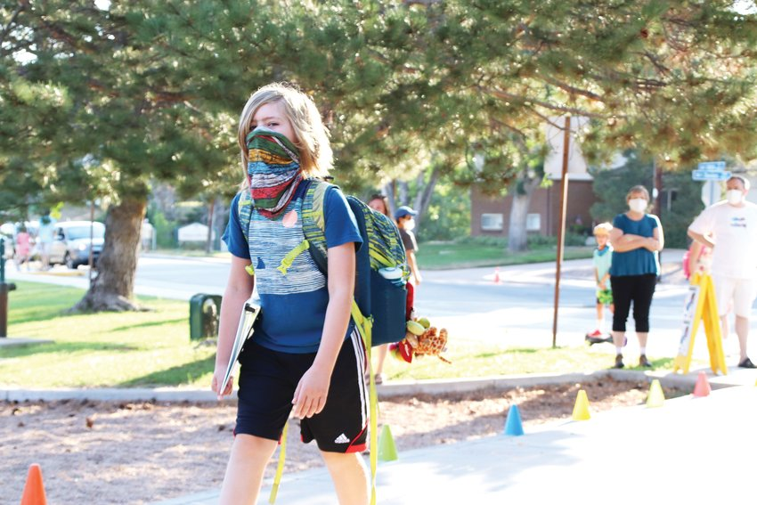 A student strides down a walkway lined with colorful cones and school staff to welcome fifth-graders back to school on Aug. 17. Masks are required in Cherry Creek School District amid the pandemic.