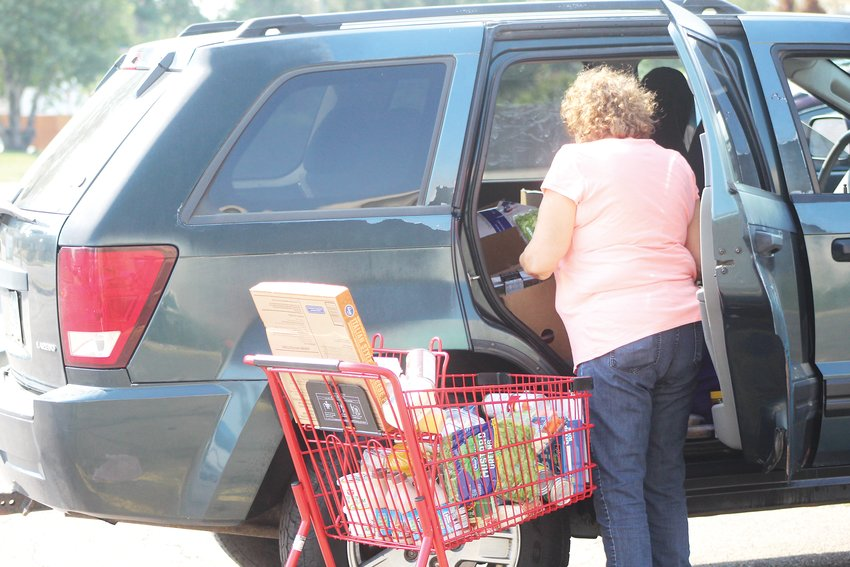 Maria packs food into her car at Community Ministry of Southwest Denver's food pantry on Aug. 20. She recently lost her house cleaning job because of the pandemic.