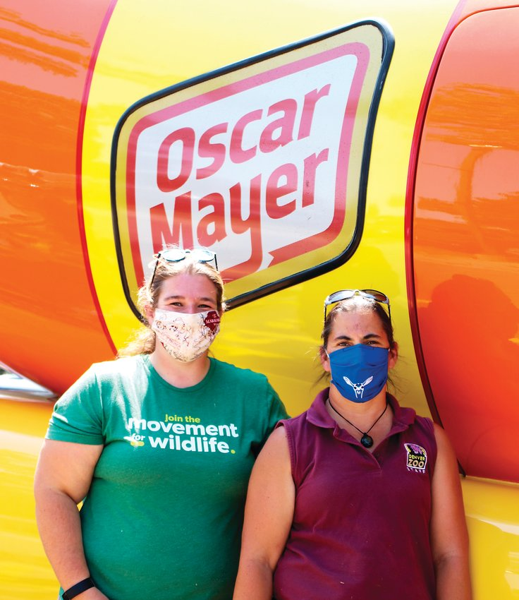 Zookeepers Jordan Baur and Christina Seely take a quick break from their duties to get their picture taken with the Oscar Mayer Wienermobile during its visit to the Denver Zoo on Aug. 19.