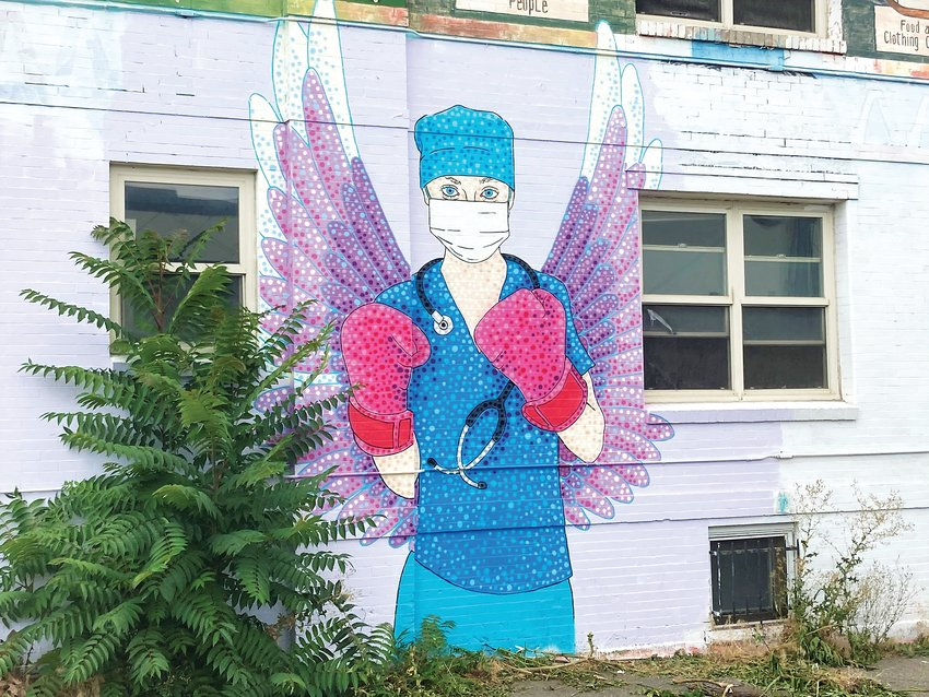 Austin Zucchini-Fowler's iconic mural of a nurse with boxing gloves on along Colfax Avenue in Capitol Hill.
