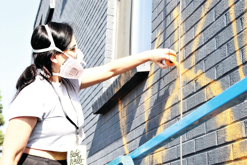 Ashley Joon sketches out her flowers on wall of a Hooker Street building in Westminster Aug. 13. She's one of 28 artists that came to Westminster to paint murals on buildings.