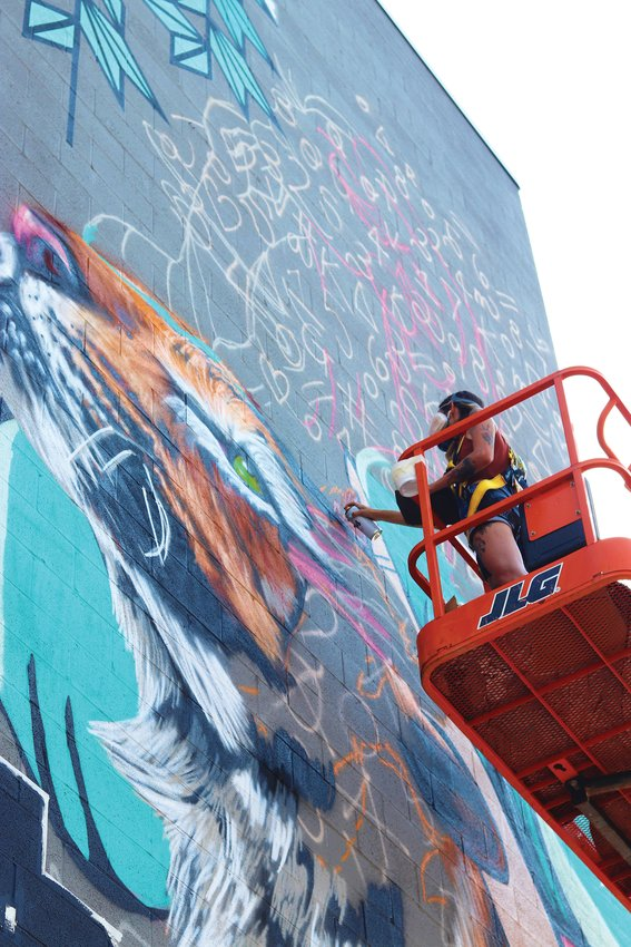 An artist paints a mural of a tiger on the side of a building in Westminster during the Babe Walls mural festival.