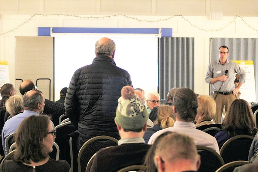 At a March 4 meeting, Denver's senior city planner, Andrew Webb (far right), listens as a member of the public speaks in opposition to Denver's proposed group living project.