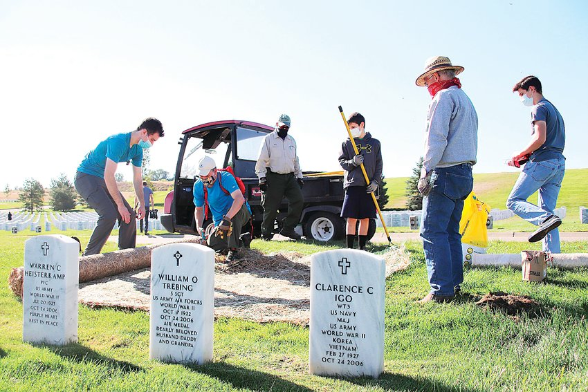 Volunteers unroll landscape matting over a bare spot on the lawn of Fort Logan National Cemetery.