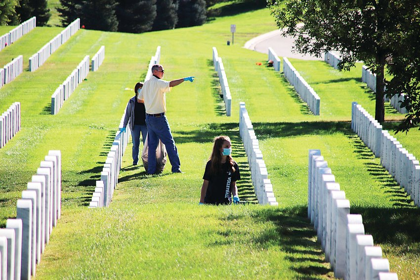 Volunteers cleaning up Fort Logan National Cemetery make their way among the headstones.