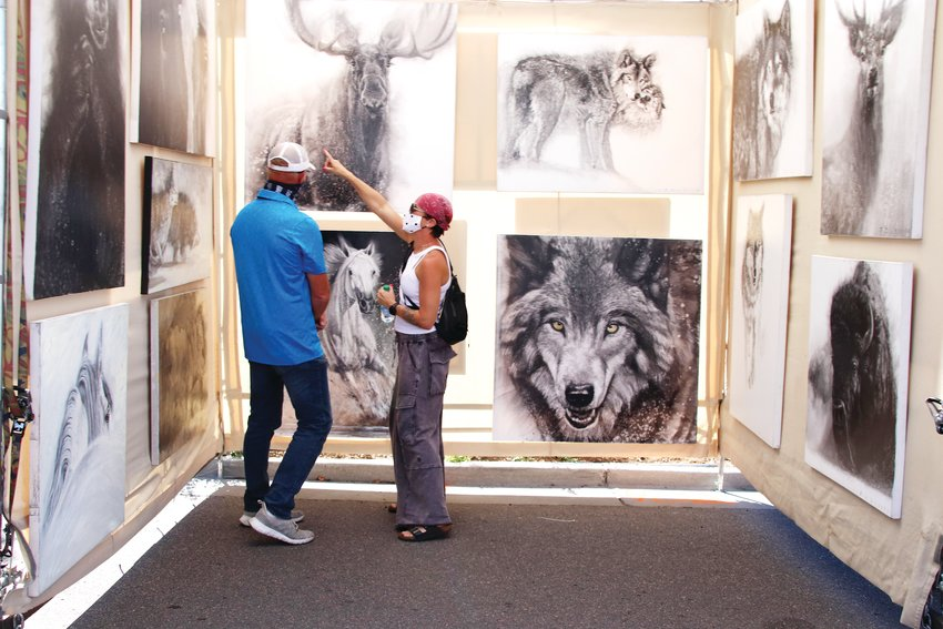 Shoppers look at an art stand during the Artfest in Castle Rock on Sept. 12.