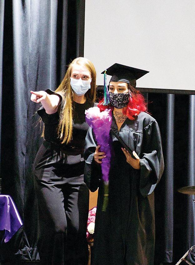 A Hope House grad takes a photo on stage after receiving her diploma.