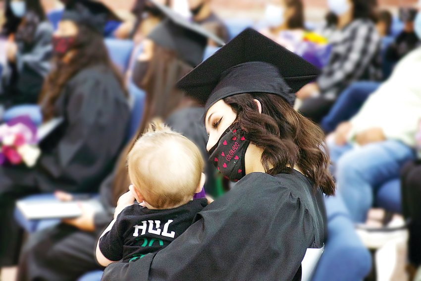 A graduating Hope House mom listens to the graduation ceremony while holding her baby, who attended the ceremony with the graduate's friends and family.