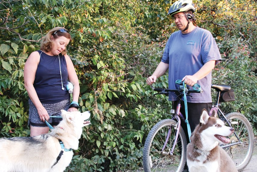 Terrie Noukirch, left, and Alex Meland chat on the High Line Canal Trail at deKoevend Park with their dogs Mishka, left, and Cocoa.
