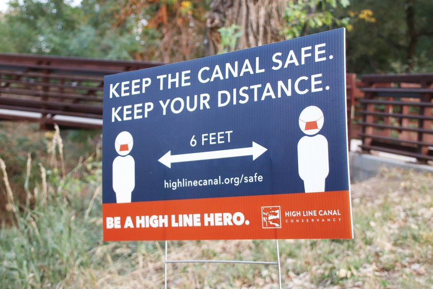 A sign encourages 6 feet of distance between people along the High Line Canal at deKoevend Park.