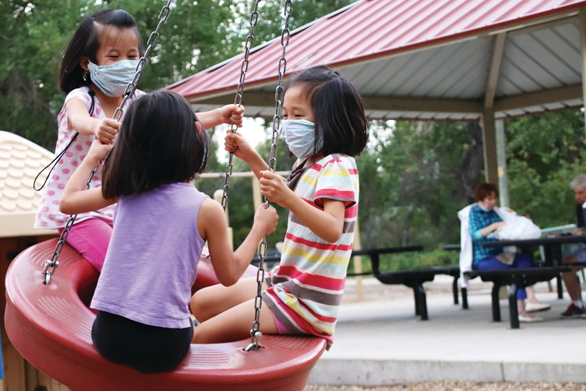 From left, Olivia, 6; Marisa, 6; and Alina, 8, use the swing at deKoevend Park Sept. 20 in west Centennial. Like some others at the park, they wore face masks.
