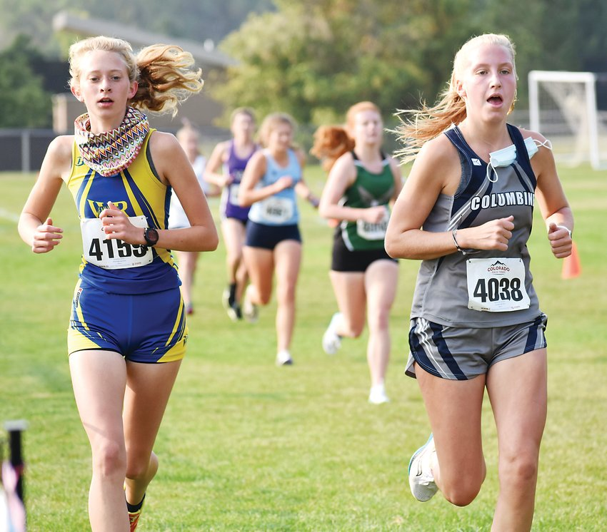 Wheat Ridge sophomore Madelyn Baillie (4159) and Columbine junior Margaret Schmitz race side-by-side toward the finish-line during the girls race of the Durden Invitational on Sept. 18.