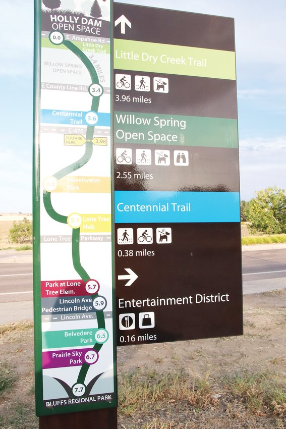 A map of local trails, parks and open space sits near a crosswalk on the Willow Creek Trail. The trailway continues north into Centennial and south to Bluffs Regional Park.
