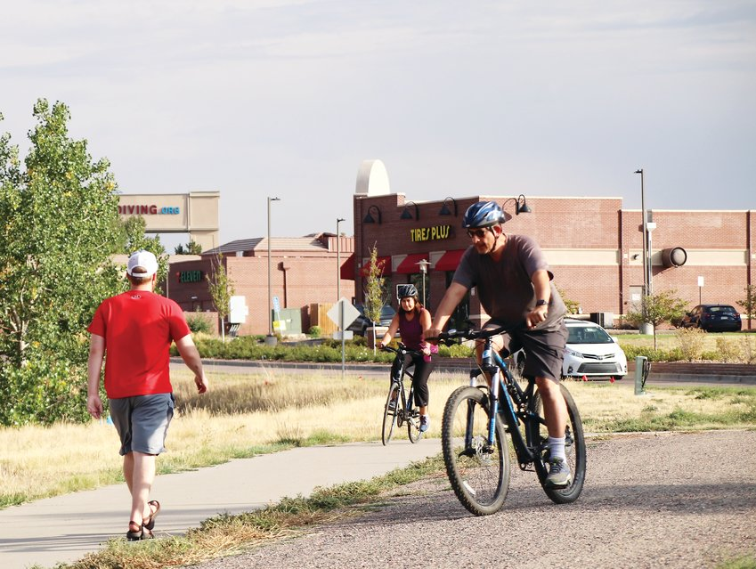 Two cyclists pass a walker on Willow Creek Trail near C-470 during rush hour. The trail continues north in Centennial and south in Lone Tree.