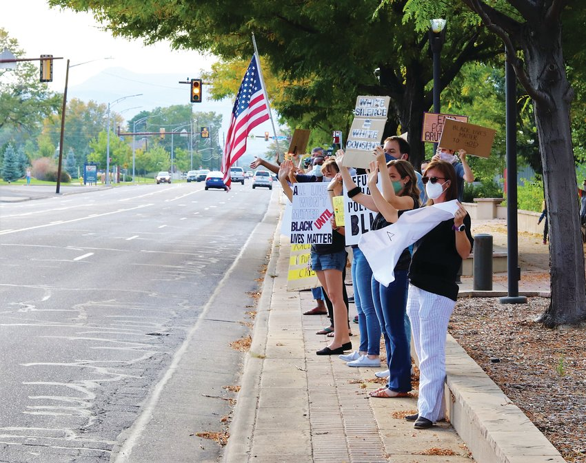 Members of Arvadans for Social Justice held signs protesting racism and police violence along Ralston Road on Sept. 21.