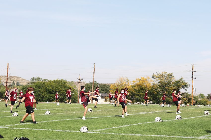 Members of the Golden High School Demons football team stretch during practice on Sept. 25 at Bell Middle School.