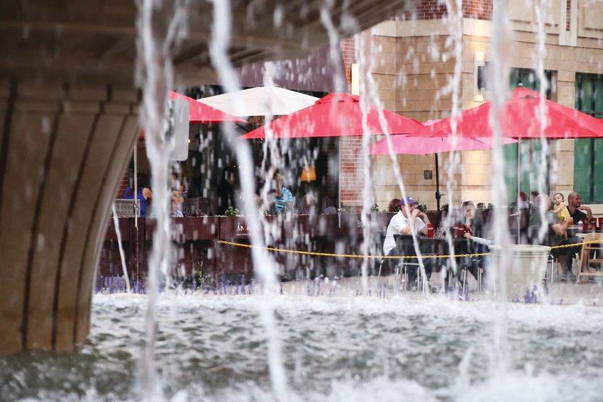 Patrons eating outdoors are seen through water falling from The Streets at SouthGlenn's fountain, where small numbers of people also gathered.