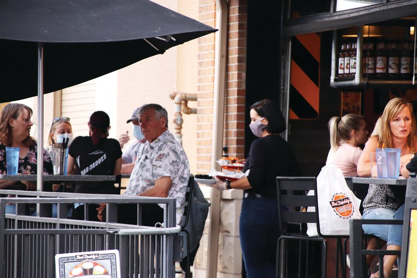 A crowd sits outside Bad Daddy's Burger Bar on Oct. 9 at The Streets at SouthGlenn outdoor mall. Dozens of patrons throughout the shopping center gathered at outdoor seating at restaurants that have adjusted to the pandemic.
