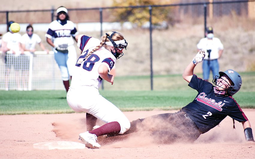 Chatfield junior Peyton Shepard (2) slides into second base as the ball gets away from Cherokee Trail shortstop Kelsey Bell (28) during the Class 5A state semifinal game Oct. 10 at Aurora Sports Park. The Chargers' season came to an end with a 5-1 loss to the Cougars.
