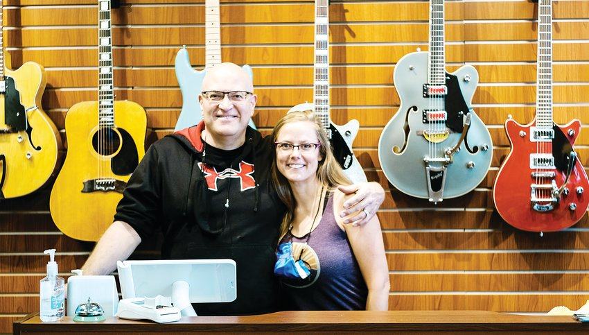 Chris Thomas and his daughter behind the counter at Spaceman Guitars in Lakewood.