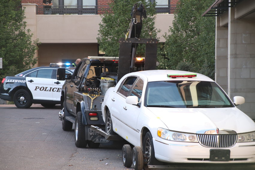 A tow truck sits with a stolen car fastened to it on Oct. 14 in Englewood after a driver in that car led police on a chase through Lakewood, Denver and Englewood.