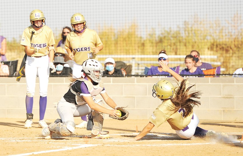 Holy Family's Carly Eldredge, right, slides safely into home, after hitting an inside the park homer in the bottom of the third inning, during a CHSAA 4A softball playoff game against Mesa Ridge Oct. 6 in Broomfield. The Tigers' 13-0 victory, propelled them into the state playoff bracket's second round. At left is Mesa Ridge catcher Aubree Krupp.