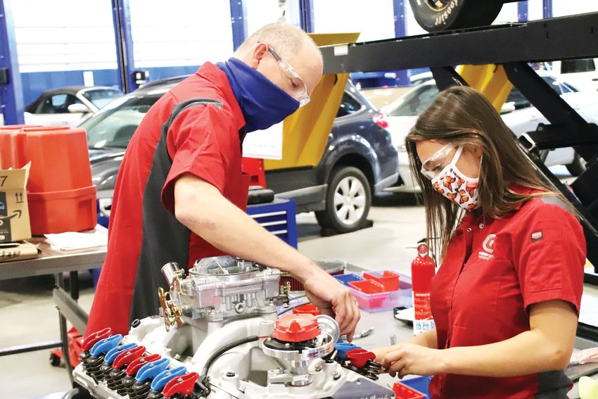Brian Manley, left, and student Taylar Oden demonstrate the kind of work they do in auto tech class at the Cherry Creek Innovation Campus.