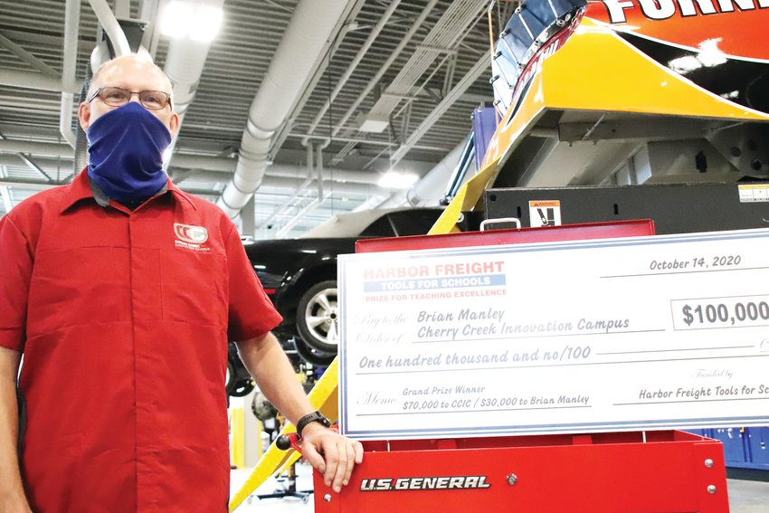 Brian Manley, an automotive technology teacher at the Cherry Creek Innovation Campus, stands next to a large honorary prize check for $100,000 at an Oct. 14 ceremony as part of the Harbor Freight Tools for Schools Prize for Teaching Excellence.