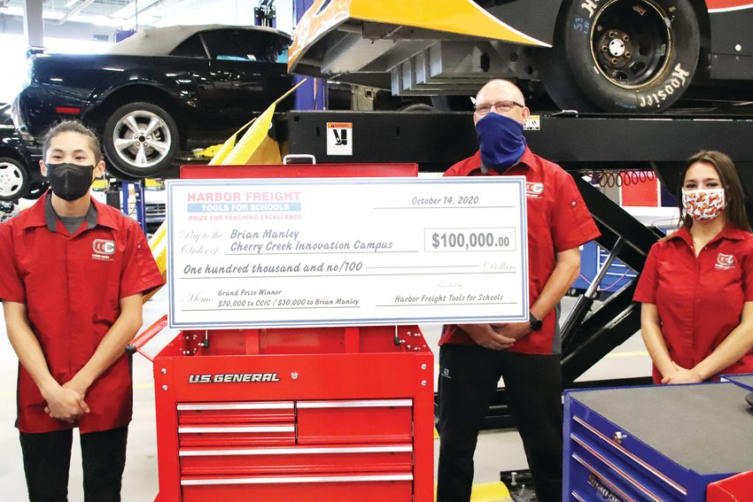 Brian Manley, in back, an automotive technology teacher at the Cherry Creek Innovation Campus, stands behind a large honorary prize check for $100,000 at an Oct. 14 ceremony as part of the Harbor Freight Tools for Schools Prize for Teaching Excellence. Manley's students Kalvin To, left, and Taylar Oden stand next to him at the Innovation Campus.