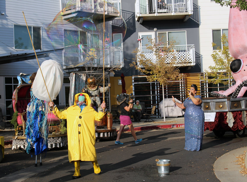 Jeff Paley, performing as the Bubble Guy, leads performers from The Handsome Little Devils group through the streets of Lakewood.