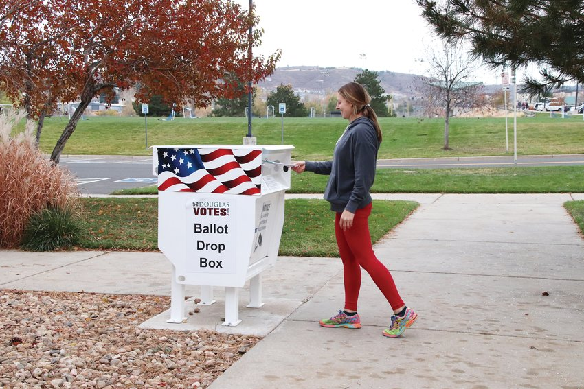 Jessica Moore of Castle Rock drops off her ballot at a walk-up location on the Douglas County Fairgrounds in town.