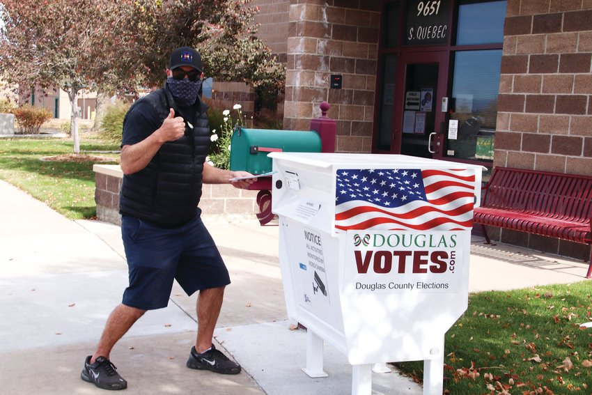 A Douglas County resident gives a thumbs up as he submits his ballot at the Douglas County Parks and Trails Division in eastern Highlands Ranch Oct. 21.
