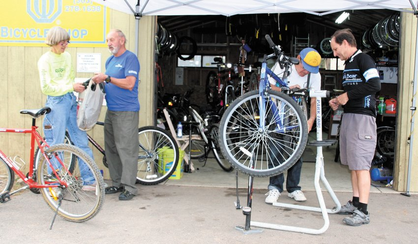 A 2015 photo of Golden Optimists volunteers at work. From left, Suzy Stutzman chats with Janusz Kokot while Howard Bagdad and Scott Perrin, far right, work on a bike's tires at the Golden Optimists' former shop location at Heritage Square.