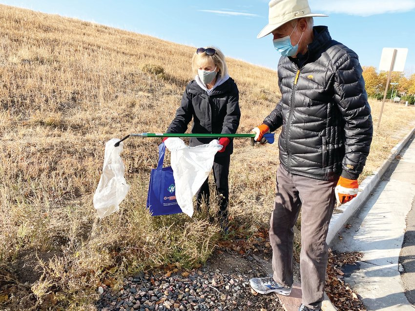 Gary Mendenhall, with the aid of his wife Susan, picks a piece of plastic out of the brush alongside Fairview Drive Oct. 24. The couple live nearby and noticed trash piling up, making their community unsightly. The Mendenhalls participated in the Lone Tree Sustainability Team trash clean up at Fairview Park, where a dozen do-gooders collected trash in roughly a two-square-mile area near Yosemite Street and Lincoln Avenue.