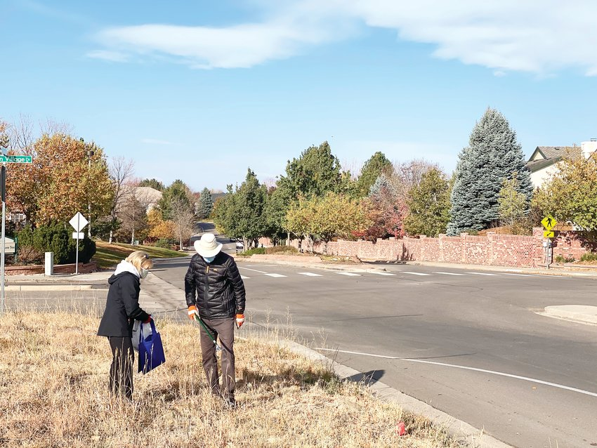 Susan and Gary Mendenhall walk along Fairview Drive in Lone Tree Oct. 24 looking for trash to clean up. Residents of the nearby Fairways neighborhood, the Mendenhalls have taken it upon themselves to maintain the unmaintained landscapes after growing tired of seeing trash accumulate on the side of the street.