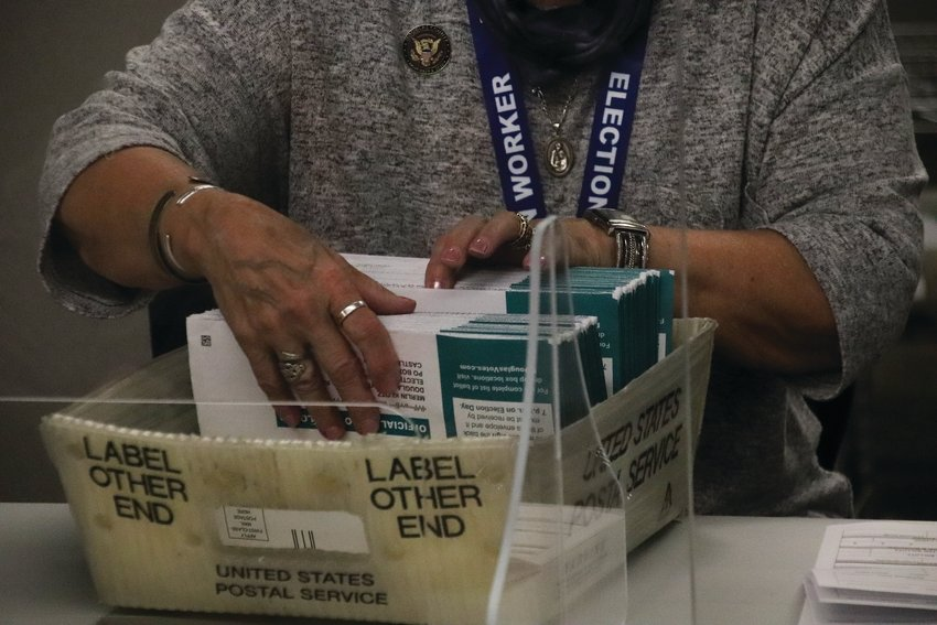 A volunteer election judge counts ballot envelopes leading up to the Nov. 3 election.