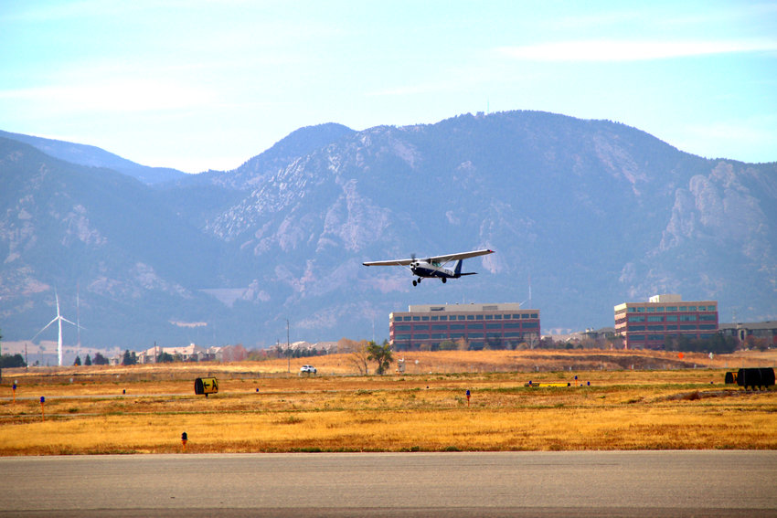 With the Colorado mountains in the background, a small aircraft takes off from Rocky Mountain Municipal Airport Oct. 22.