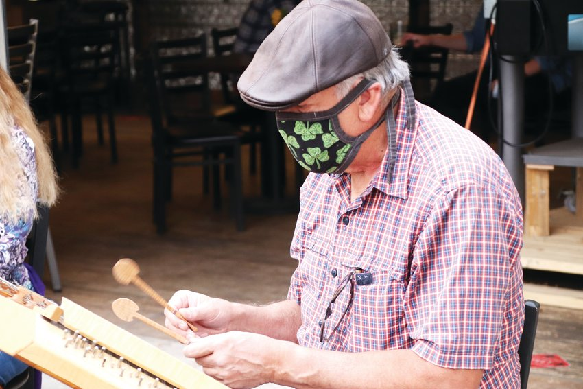 John Hammer, 69, of Littleton, plays the hammered dulcimer outside of the Brewability brewery — formerly the location of the Brew on Broadway — in downtown Englewood in October. Hammer's band, Fennec, has played Celtic music around the Denver metro area for years.