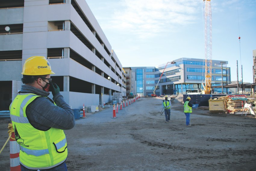 Kiewit's 400,000 square-foot campus is starting to take shape. Facing the front door of the first building, Eric Roumph, project manager, adjusts his face mask--just one of the protocols Kiewit required of employees on its site since the pandemic started.