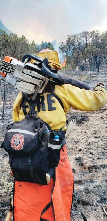 North Metro Fire and Rescue Lt. Mike Anderson hauls gear as prepares to engage with a portion of the Pine Gulch fire North of Grand Junction this summer. It's one of four blazes the team faced this summer, in Colorado and Northern California.