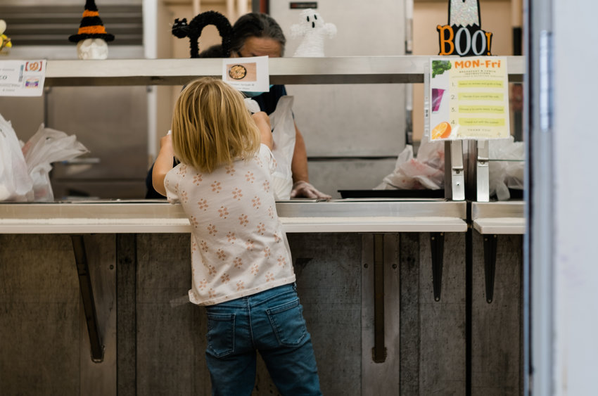 A kindergartner reaches for her lunch at Foothills, Elementary in Lakewood, Colorado.