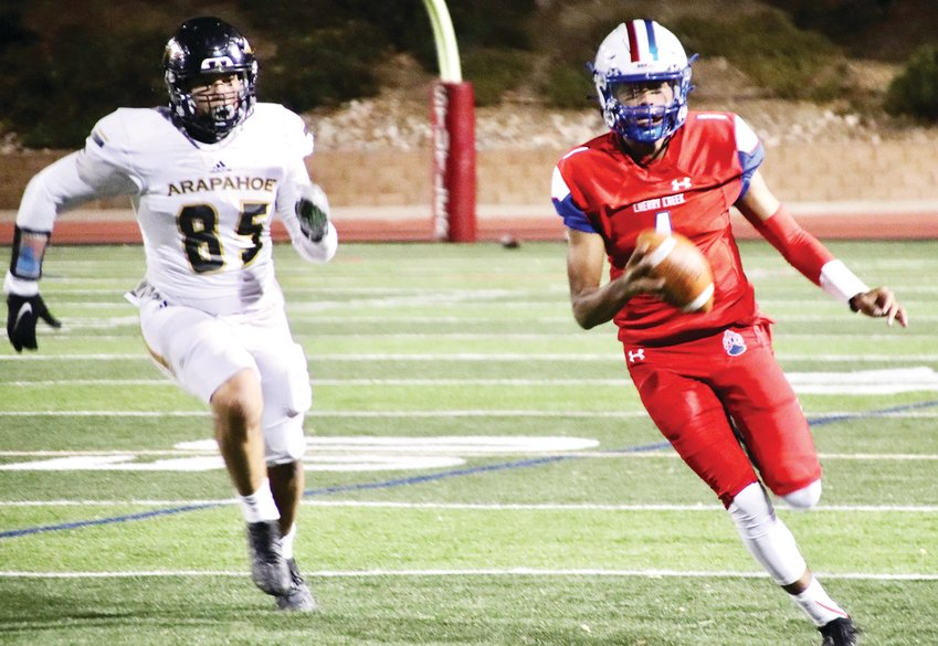 Arapahoe's Jared Ramos (85) chases Cherry Creek quarterback Julian Hammond (1) after he scrambled out of the pocket during the second quarter of the Nov. 6 Centennial League football game. The Bruins, the top-ranked team in the CHSAANow.com 5A poll, defeated the Warriors, 56-7.