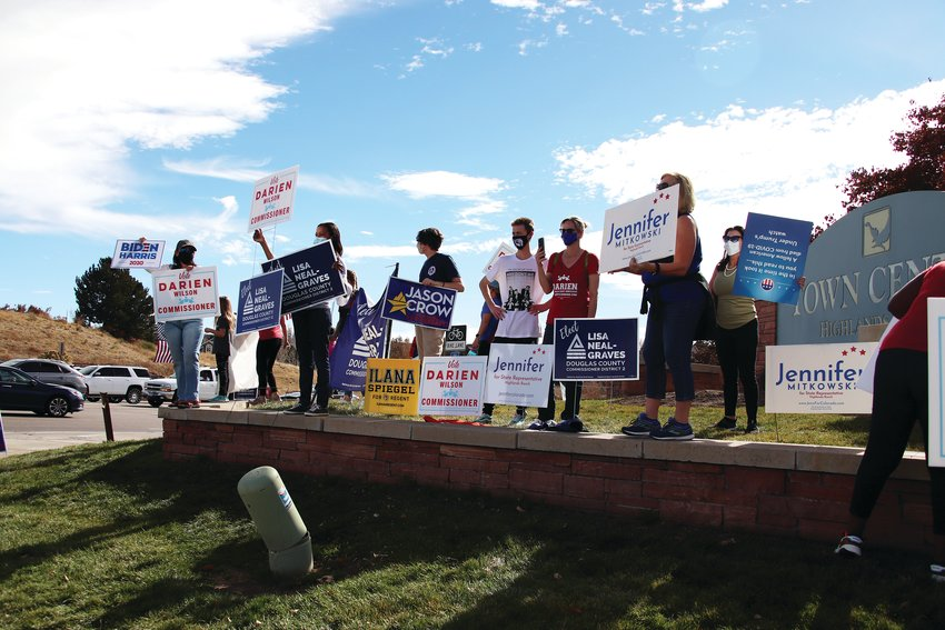 Supporters of Democrats in local, state and national elections stand at a street corner in Highlands Ranch on Election Day.