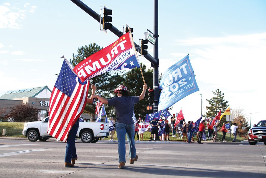 Supporters of President Donald Trump stand at the corner of Highlands Ranch Parkway and University Boulevard on Election Day.