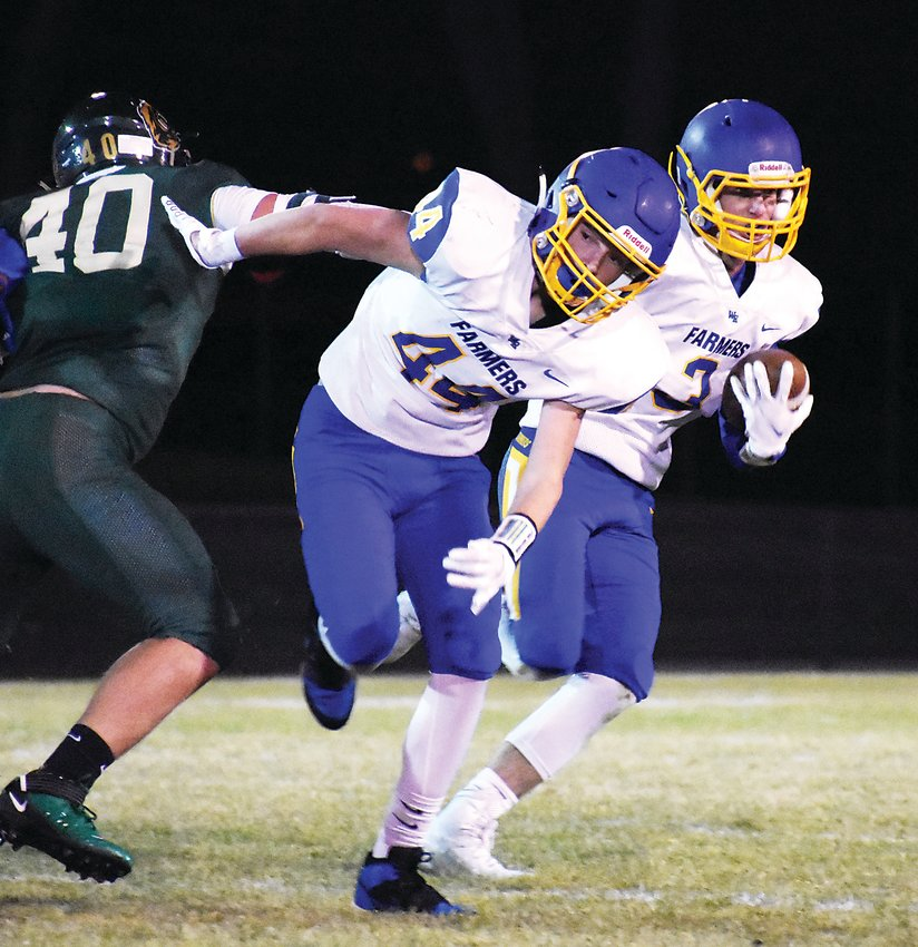 Wheat Ridge senior Sam McDonough (3) picks up a block by senior Jack Vaugh (44) during a run in the first half Nov. 6 at Jeffco Stadium. The Farmers suffered a 46-25 loss in the Class 4A Jeffco League game.