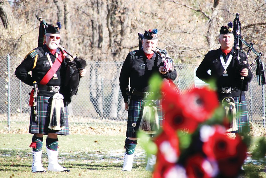The El Jebel Shrine bagpipe band watches from a distance.