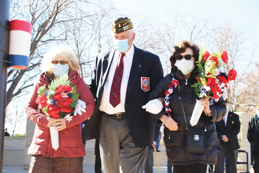 Elizabeth Marzonie, left, her husband James Marzonie, and Shirley Baldaccini carry poppies -- a traditional symbol of Veterans Day -- to the flagpole at the World War II Memorial at Ketring Park.